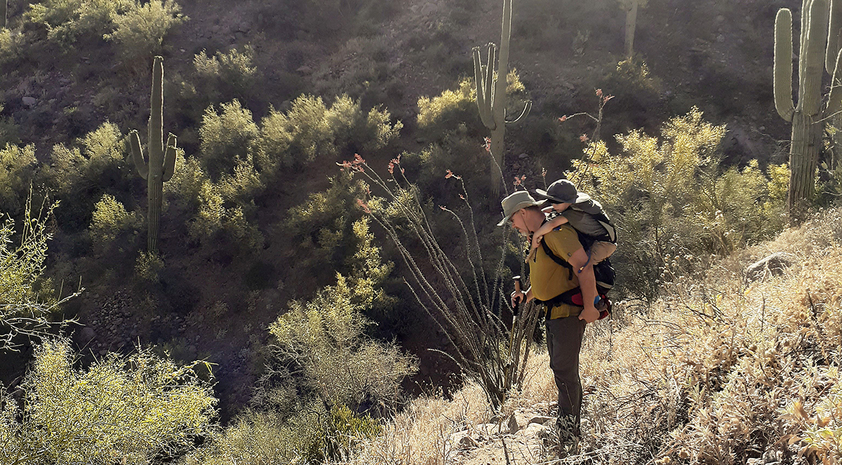 Grandfather carries his grandson in a backpack while on a hike in the desert